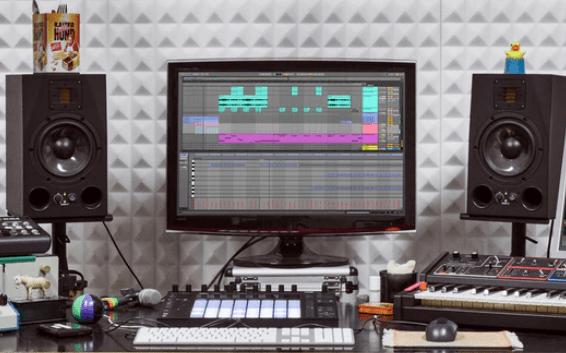un home studio : écran, haut-parleurs, claviers et contrôleurs midi