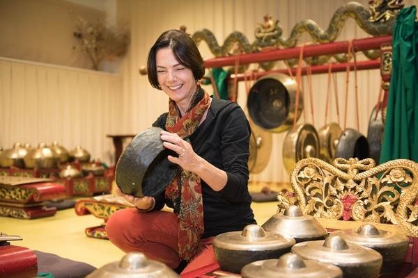 Sylvie Chantriaux souriante et assie au centre de son gamelan javanais Kyai Kumandang